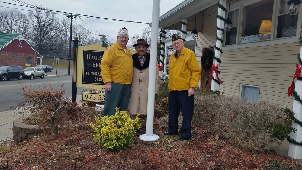 A photo of three gentleman standing beside a flag pole